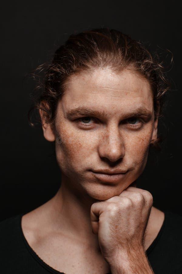 Πορτρέτο ενός όμορφου μακρυμάλλους ατόμου με τη συρμένη τρίχα και των φακίδων που φορούν μια μαύρη μπλούζα στοκ εικόνες