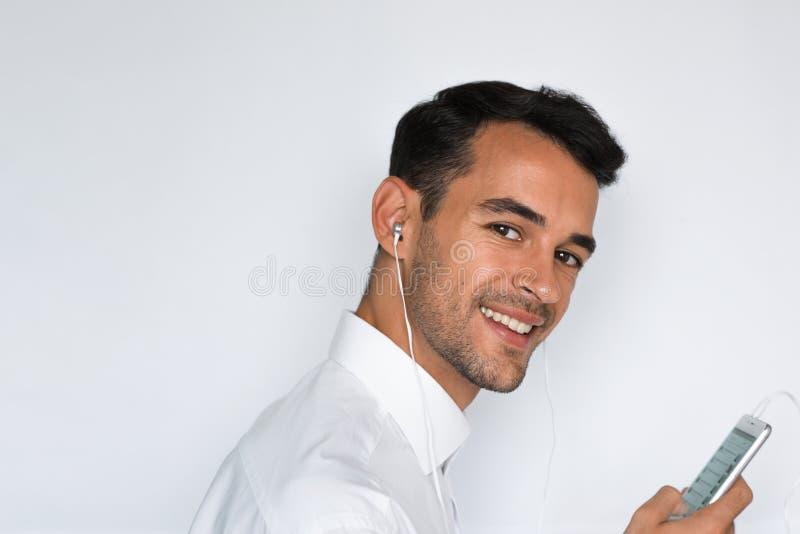 Πορτρέτο ενός όμορφου νεαρού άνδρα στο άσπρο πουκάμισο με τα ακουστικά που κρατά το κινητό τηλέφωνο απομονωμένο στο ανοικτό γκρι  στοκ εικόνες