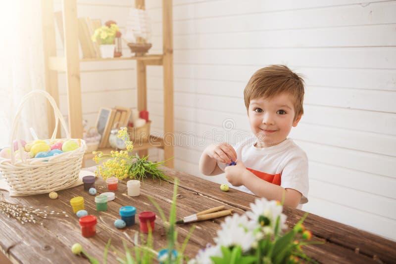Πορτρέτο ενός χαριτωμένου αγοριού 3 χρονών Κρατά τη βούρτσα και χρωματίζει τα αυγά Πάσχας στοκ εικόνα με δικαίωμα ελεύθερης χρήσης
