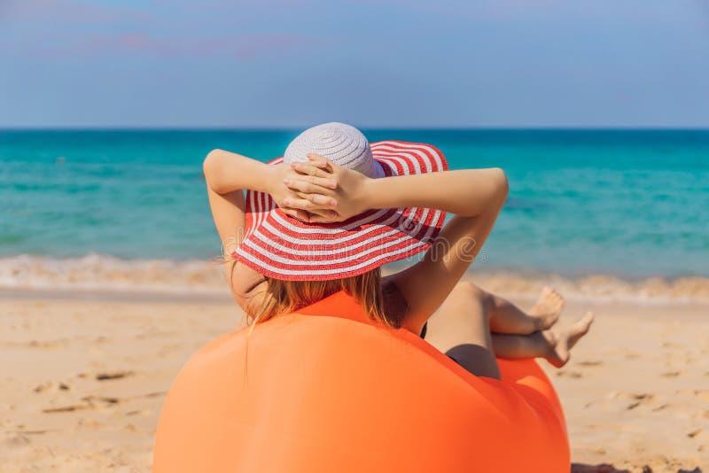 Πορτρέτο θερινού τρόπου ζωής της όμορφης συνεδρίασης κοριτσιών στον πορτοκαλή διογκώσιμο καναπέ στην παραλία του τροπικού νησιού  στοκ εικόνα