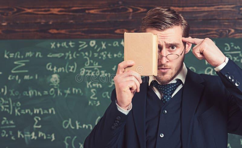 Πορτρέτο κινηματογραφήσεων σε πρώτο πλάνο του βιβλίου εκμετάλλευσης σπουδαστών μπροστά από το πρόσωπό του και του πιέζοντας δάχτυ στοκ εικόνα
