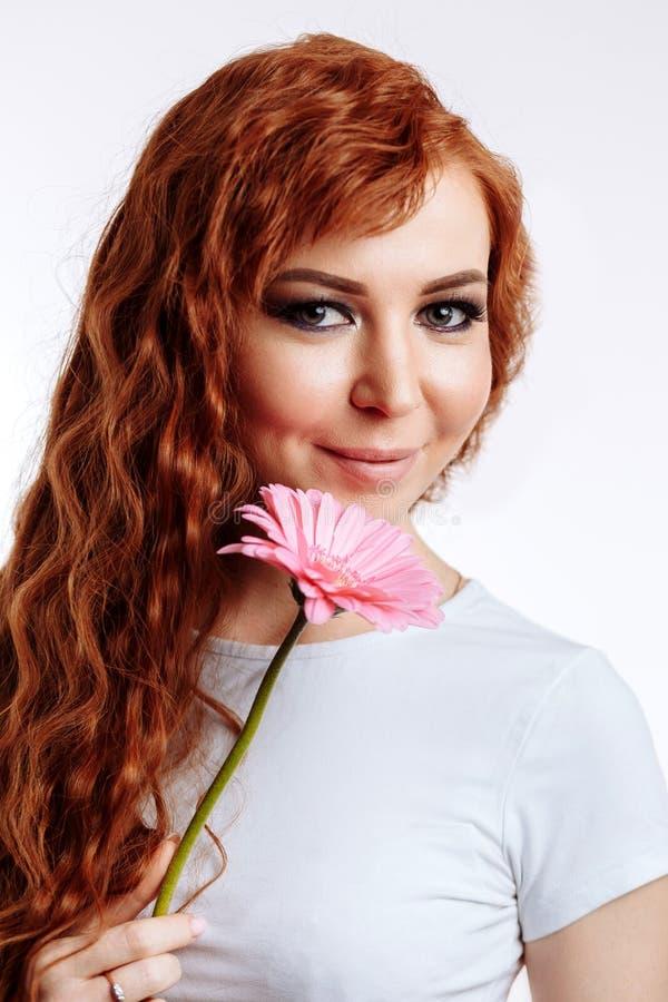 Πορτρέτο μιας αρκετά καυκάσιας γυναίκας που χαμογελά και που κρατά το λουλούδι στοκ φωτογραφίες