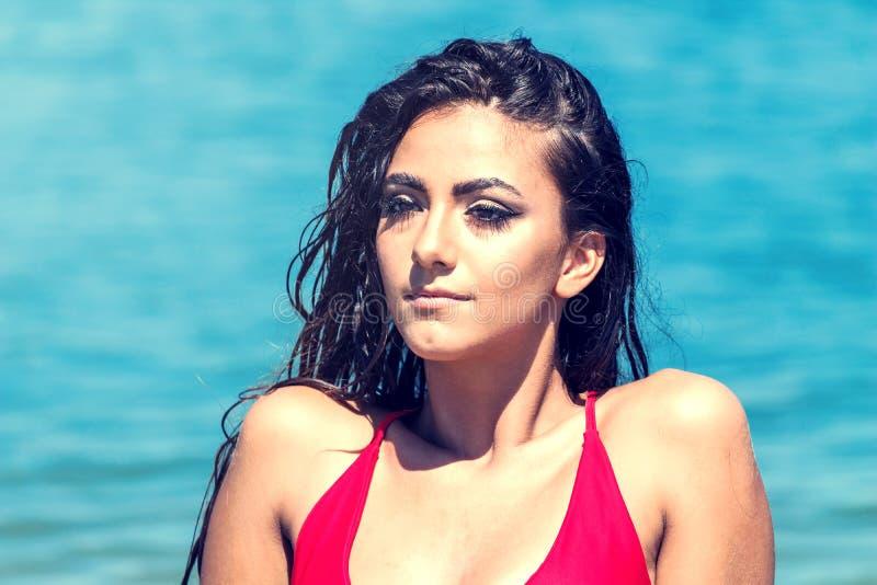 Πορτρέτο μιας όμορφης γυναίκας στο κόκκινο μπικίνι στην παραλία στοκ εικόνες με δικαίωμα ελεύθερης χρήσης