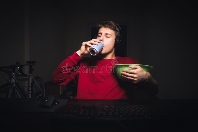 Πορτρέτο μιας συνεδρίασης νεαρών άνδρων τη νύχτα σε ένα δωμάτιο κοντά σε έναν υπολογιστή με ένα πιάτο των πρόχειρων φαγητών στα χ στοκ φωτογραφίες με δικαίωμα ελεύθερης χρήσης