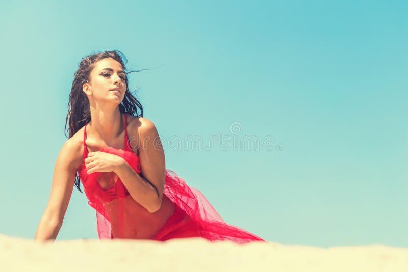 Πορτρέτο μόδας ενός νέου κοριτσιού σε ένα κόκκινο φόρεμα στο υπόβαθρο μπλε ουρανού και άμμου στοκ εικόνα
