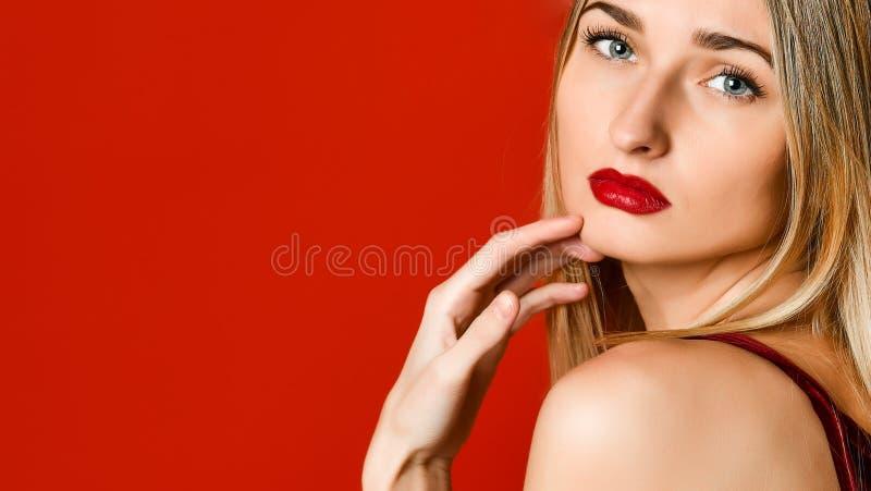 Πορτρέτο μόδας της σεξουαλικής ξανθής γυναίκας με τα προκλητικά στιλπνά κόκκινα χείλια πέρα από το κόκκινο υπόβαθρο στοκ εικόνες