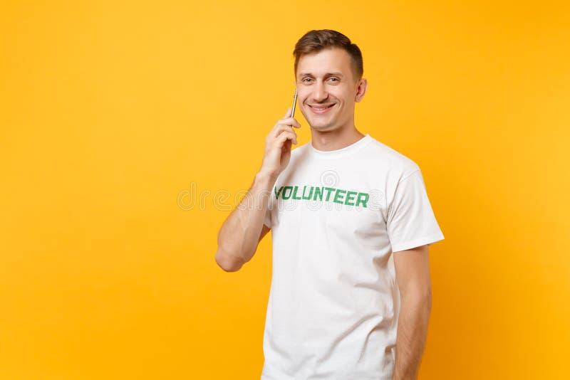 Πορτρέτο νεαρών άνδρων στην άσπρη μπλούζα με τη γραπτή επιγραφή πράσινος τίτλος εθελοντική ομιλία στο κινητό τηλέφωνο που απομονώ στοκ εικόνες
