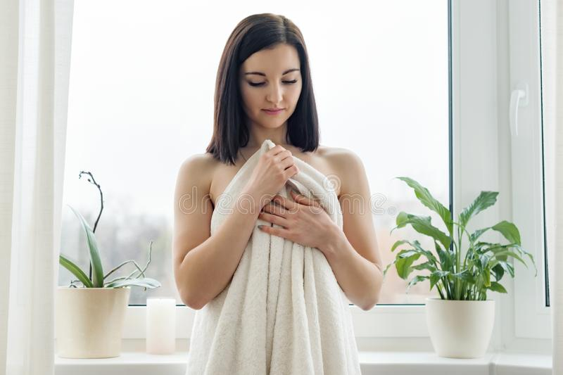 Πορτρέτο ομορφιάς της νέας γυναίκας brunette στην πετσέτα λουτρών, SPA στο σπίτι Γυναίκα που στέκεται κοντά στο παράθυρο, που εξε στοκ εικόνα