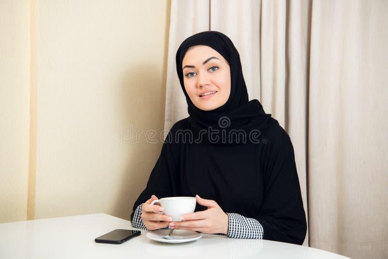 Πορτρέτο της ελκυστικής ασιατικής φθοράς γυναικών hijab απολαμβάνοντας τον καφέ και χαμογελώντας στη κάμερα στοκ εικόνα