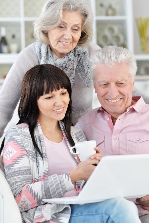 Πορτρέτο της ευτυχούς οικογένειας με το lap-top που θέτει στο σπίτι στοκ εικόνες με δικαίωμα ελεύθερης χρήσης