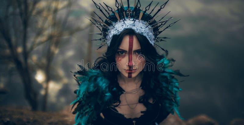 Πορτρέτο της νέας γυναίκας στην εικόνα μιας νεράιδας και μιας μάγισσας που στέκονται πέρα από μια λίμνη στοκ φωτογραφία