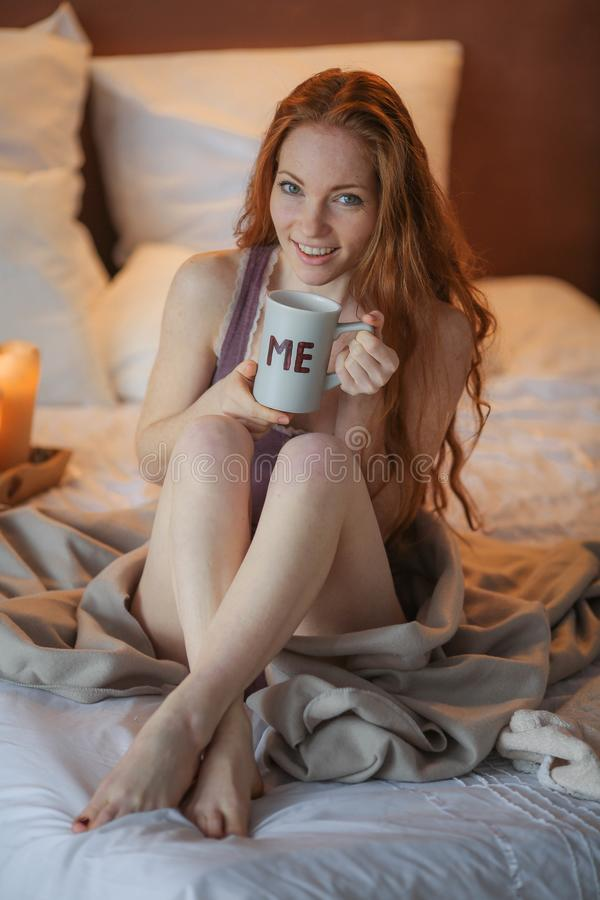 Πορτρέτο της νέας όμορφης γυναίκας τα χέρια της που κρατούν τον κρύο χειμώνα πρωινού φλιτζανιών του καφέ στην άσπρη κρεβατοκάμαρά στοκ φωτογραφίες