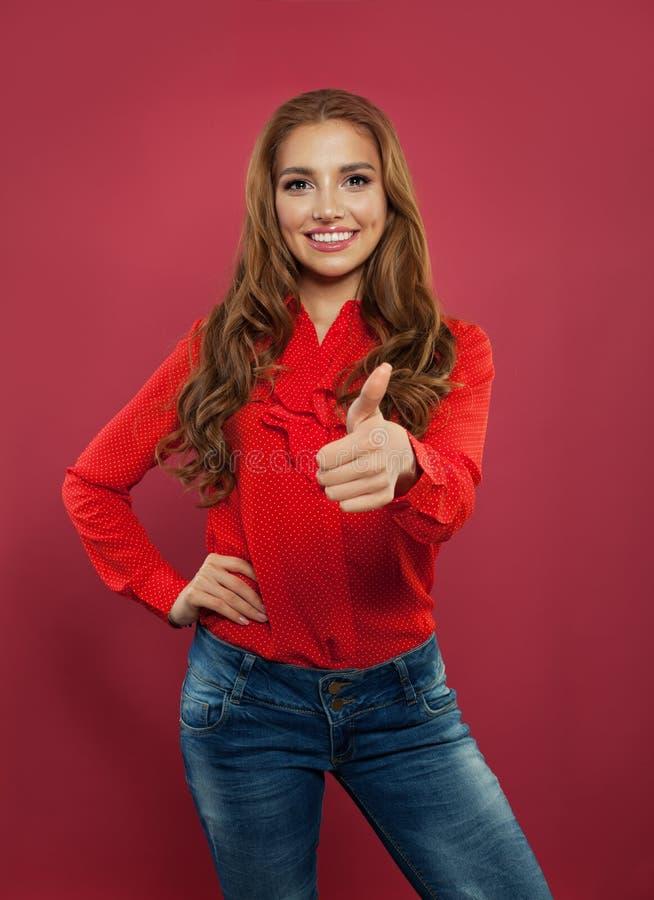 Πορτρέτο της νέας όμορφης γυναίκας που παρουσιάζει αντίχειρα στο ρόδινο υπόβαθρο Ευτυχές κορίτσι σπουδαστών, θετικές συγκινήσεις στοκ εικόνες με δικαίωμα ελεύθερης χρήσης