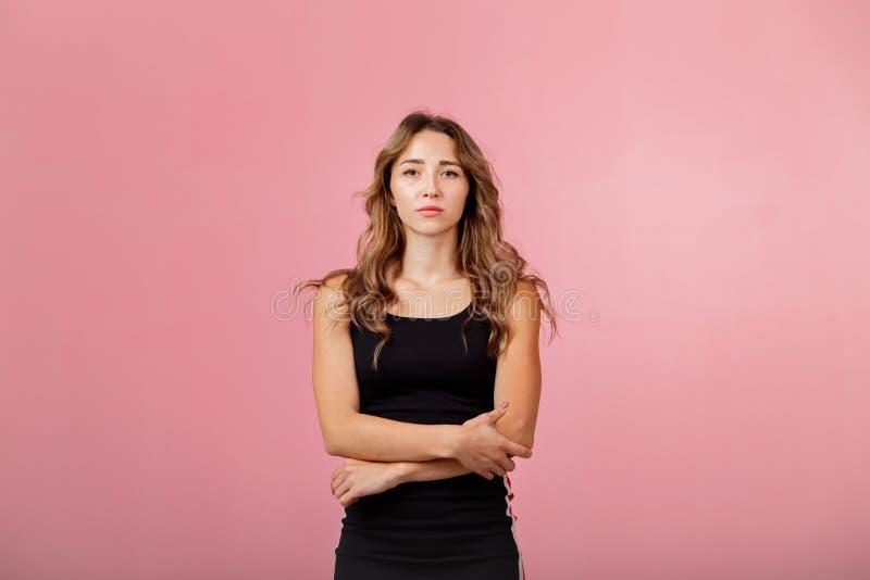 Πορτρέτο της νέας στοχαστικής ξανθής γυναίκας που φορά το μαύρο φόρεμα στο ρόδινο κλίμα στοκ εικόνα