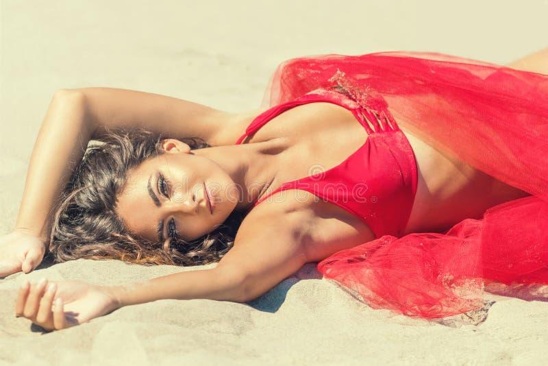 Πορτρέτο της όμορφης γυναίκας που βρίσκεται στην άμμο στοκ εικόνα με δικαίωμα ελεύθερης χρήσης