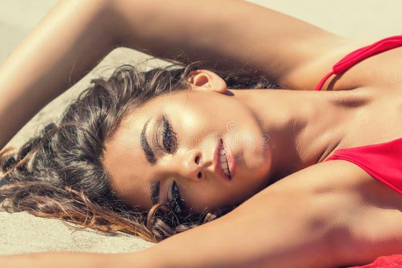 Πορτρέτο της όμορφης γυναίκας που βρίσκεται στην άμμο στοκ εικόνες