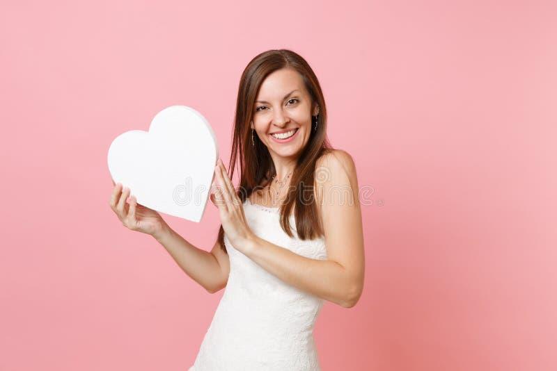 Πορτρέτο της χαμογελώντας χαρούμενης γυναίκας νυφών στην όμορφη άσπρη άσπρη καρδιά εκμετάλλευσης γαμήλιων φορεμάτων μόνιμη με το  στοκ εικόνες