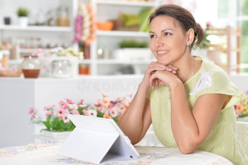 Πορτρέτο της χαριτωμένης νέας γυναίκας που χρησιμοποιεί την ψηφιακή ταμπλέτα στοκ εικόνα