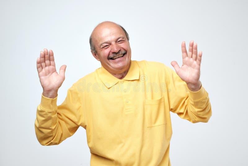 Πορτρέτο του ανώτερου ευτυχούς ατόμου με τα χέρια που ανυψώνονται προς τα πάνω στοκ φωτογραφία