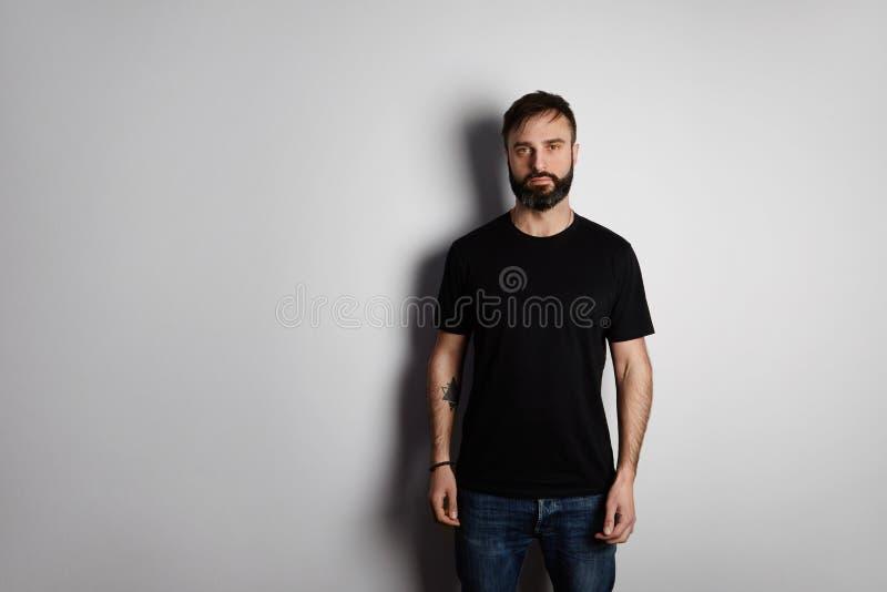 Πορτρέτο του γενειοφόρου ατόμου στη μαύρη μπλούζα στο κενό υπόβαθρο στοκ εικόνες