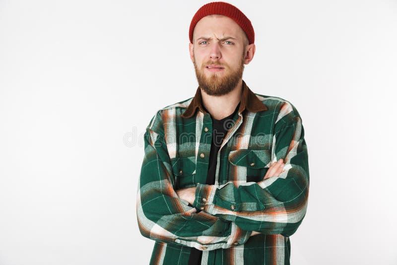 Πορτρέτο του ελκυστικού γενειοφόρου τύπου που φορά το πουκάμισο καπέλων και καρό, στάση που απομονώνεται πέρα από το άσπρο υπόβαθ στοκ εικόνες