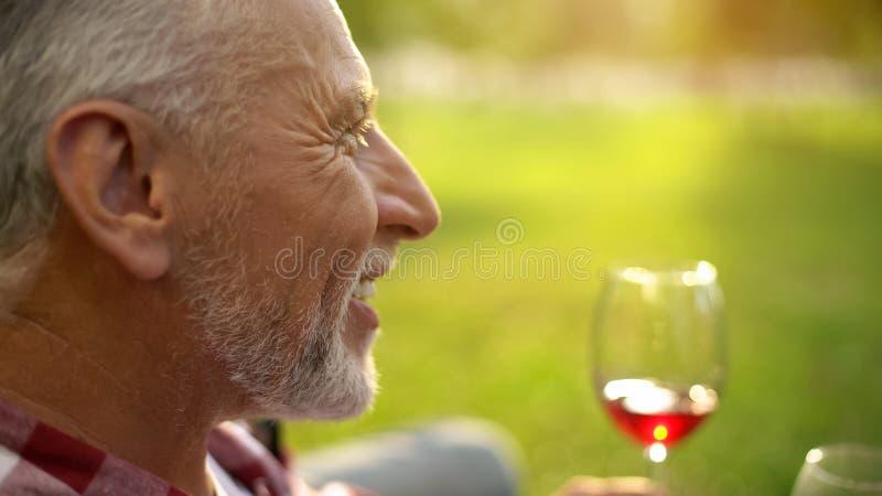 Πορτρέτο του ευτυχούς συνταξιούχου χαμόγελου αρσενικών και του κρασιού κατανάλωσης με τη σύζυγο, επέτειος στοκ εικόνες