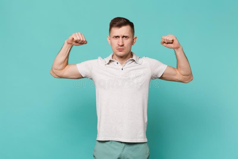 Πορτρέτο του ισχυρού νεαρού άνδρα στα περιστασιακά ενδύματα που στέκονται, που παρουσιάζει δικέφαλους μυς, μυ'ες που απομονώνοντα στοκ εικόνες