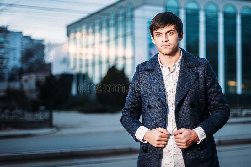 Πορτρέτο του καθιερώνοντος τη μόδα όμορφου κομψού νέου ατόμου μόδας στο παλτό στην οδό που εξισώνει υπαίθρια στοκ φωτογραφία με δικαίωμα ελεύθερης χρήσης