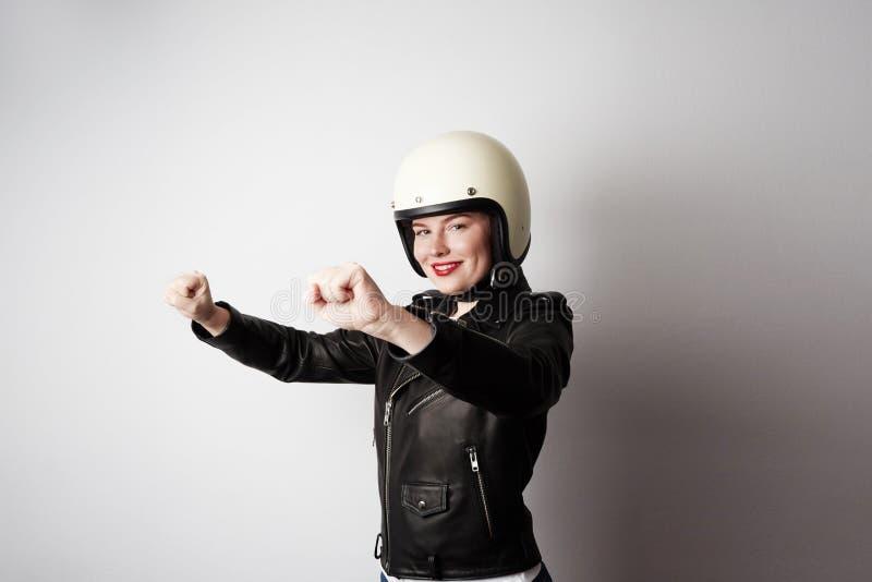 Πορτρέτο του καθιερώνοντος τη μόδα όμορφου κοριτσιού στο μαύρο σακάκι δέρματος που προσποιείται να οδηγήσει μια μοτοσικλέτα στο ά στοκ εικόνες