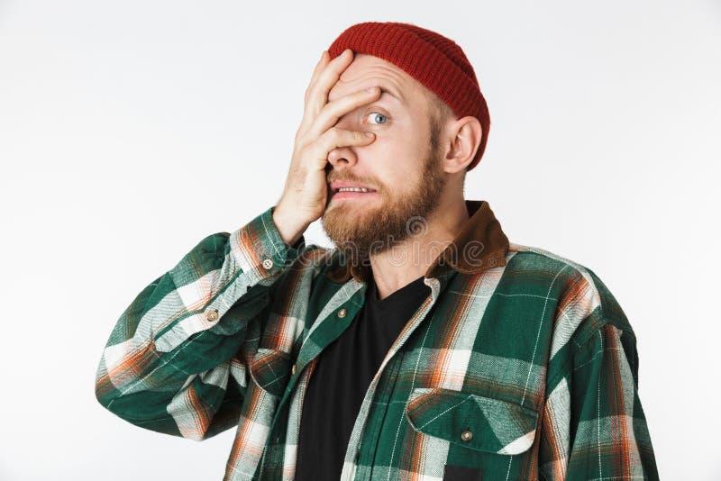 Πορτρέτο του νευρικού ατόμου που φορά το πουκάμισο καπέλων και καρό που αρπάζει το πρόσωπό του, στεμένος που απομονώνεται πέρα απ στοκ φωτογραφία με δικαίωμα ελεύθερης χρήσης