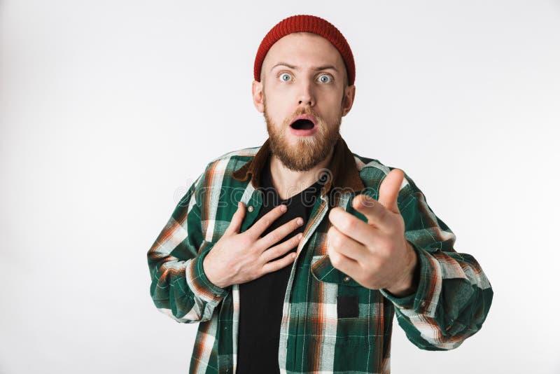 Πορτρέτο του συγκλονισμένου γενειοφόρου ατόμου που φορά το πουκάμισο καπέλων και καρό που αναρωτιέται, στεμένος που απομονώνεται  στοκ φωτογραφία