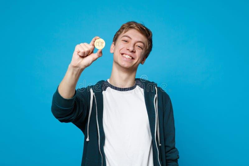 Πορτρέτο του χαμογελώντας νεαρού άνδρα στα περιστασιακά ενδύματα που κρατά bitcoin, μελλοντικό νόμισμα που απομονώνεται στο μπλε  στοκ φωτογραφίες