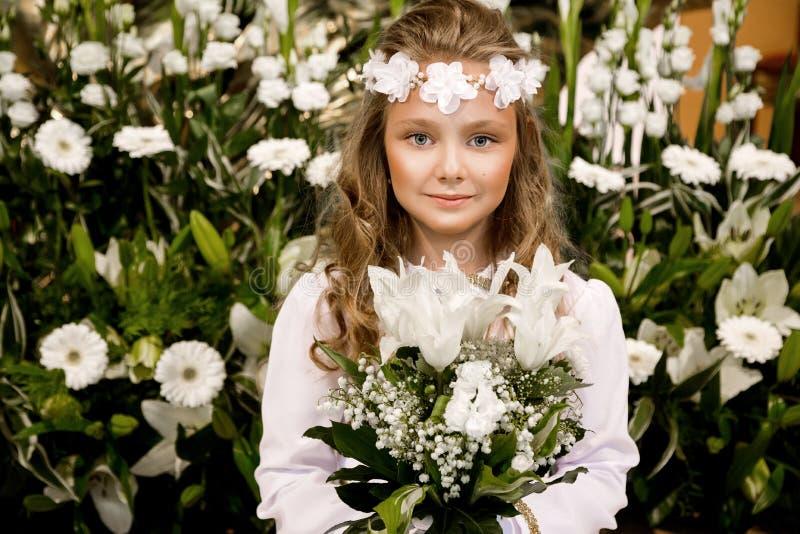 Πορτρέτο του χαριτωμένου μικρού κοριτσιού στο άσπρο φόρεμα και του στεφανιού στην πρώτη ιερή πύλη εκκλησιών υποβάθρου κοινωνίας στοκ εικόνα με δικαίωμα ελεύθερης χρήσης