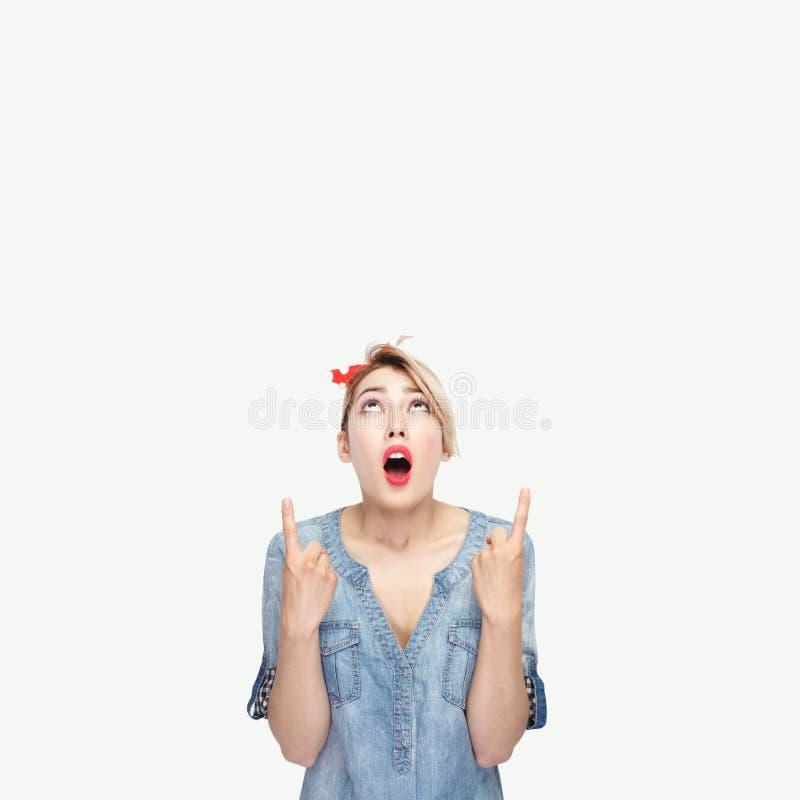 Πορτρέτο που διεγείρεται της όμορφης νέας γυναίκας στο περιστασιακό μπλε πουκάμισο τζιν, makeup, κόκκινη headband στάση εξετάζοντ στοκ εικόνες