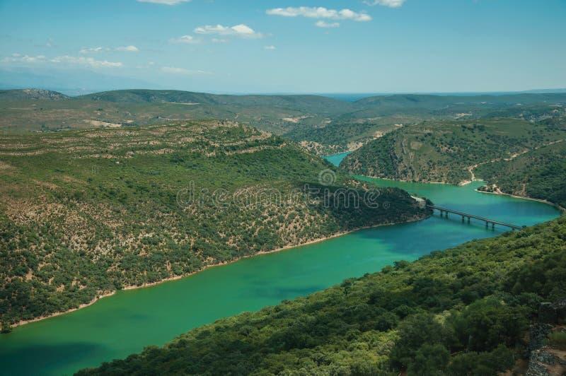 Ποταμός και γέφυρα Tagus σε μια κοιλάδα με τους λόφους που καλύπτονται από τα δέντρα στοκ εικόνες