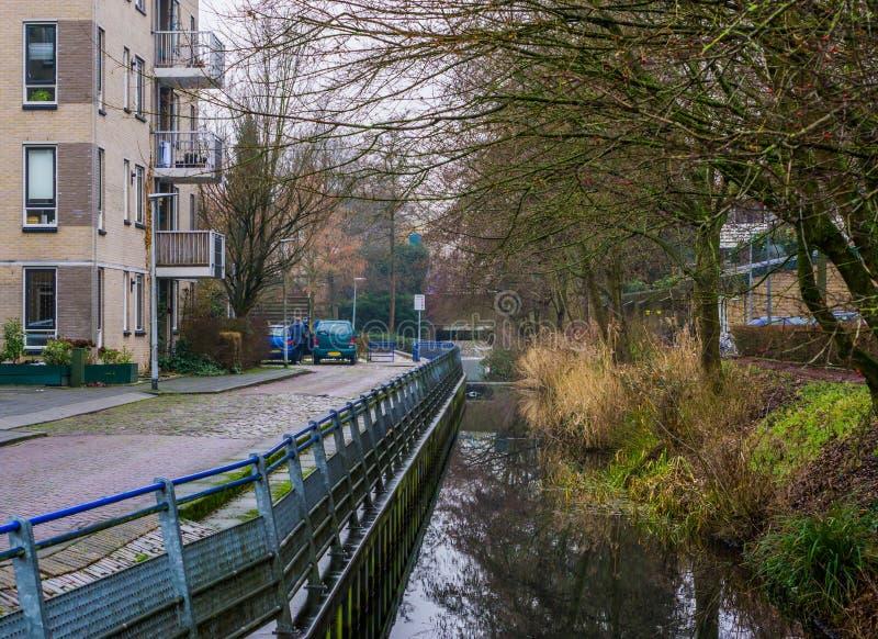 Ποταμός που τρέχει μέσω των οδών μιας γειτονιάς, υπαίθρια αρχιτεκτονική του Χίλβερσουμ, οι Κάτω Χώρες στοκ φωτογραφία