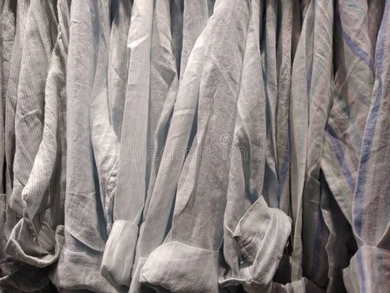 Πουκάμισα, πουκάμισα που κρεμιούνται στις κρεμάστρες σε ένα ράφι ιματισμού στοκ εικόνες με δικαίωμα ελεύθερης χρήσης