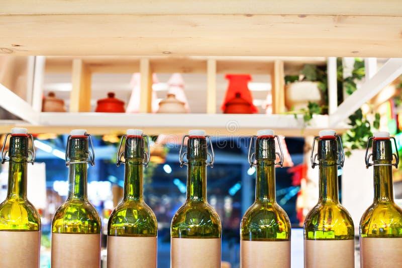 Πράσινα μπουκάλια γυαλιού του κρασιού στη γραμμή στο ξύλινο ράφι, εσωτερικό σχέδιο φραγμών, έννοια δοκιμής κρασιού, ύφος νυχτεριν στοκ εικόνες