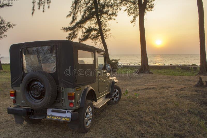 Πράσινο ινδικό SUV στην ξηρά χλόη στα πλαίσια των δέντρων και ηλιοβασίλεμα πέρα από τον ωκεανό στοκ εικόνα
