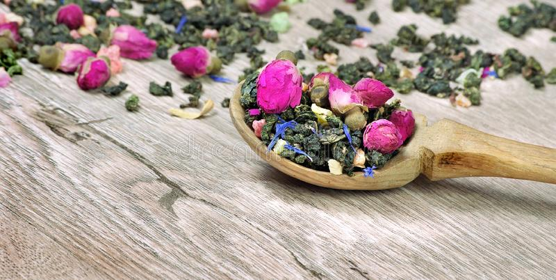 πράσινο τσάι πράσινο τσάι με τα λουλούδια σε ένα ξύλινο κουτάλι πράσινο τσάι με τα λουλούδια και τα κομμάτια φρούτων τσάι μίγματο στοκ φωτογραφία