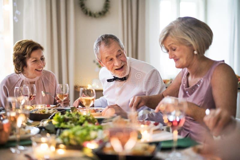 Πρεσβύτεροι που κάθονται στον πίνακα σε μια εσωτερική οικογενειακή γιορτή γενεθλίων, κατανάλωση στοκ εικόνα με δικαίωμα ελεύθερης χρήσης