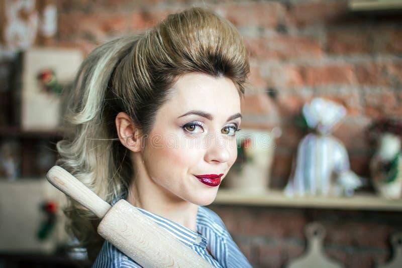 Προκλητικό χαμογελώντας κορίτσι με την κυλώντας καρφίτσα στον ώμο της στην κουζίνα Η προκλητική νέα γυναίκα ξανθή προετοιμάζει τη στοκ φωτογραφία με δικαίωμα ελεύθερης χρήσης