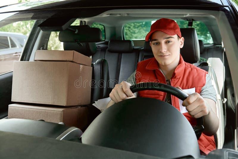 Προσπάθεια να γίνει η εργασία του εγκαίρως Συνεδρίαση ατόμων παράδοσης χαμόγελου στο αυτοκίνητο ως οδηγό Μπροστινή όψη στοκ εικόνα