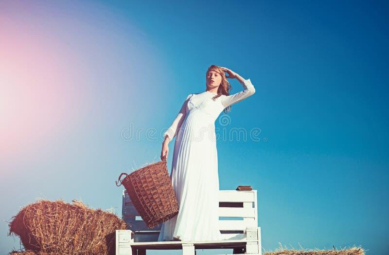 Πρότυπο μόδας στο μπλε ουρανό Albino ψάθινο καλάθι λαβής κοριτσιών με το σανό στο ηλιόλουστο υπαίθριο πικ-νίκ Νύφη γυναικών στο γ στοκ εικόνες