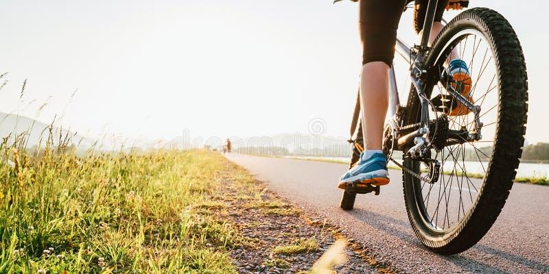 Πόδια γυναικών στο πεντάλι bycikle στο φως ηλιοβασιλέματος στοκ φωτογραφίες με δικαίωμα ελεύθερης χρήσης