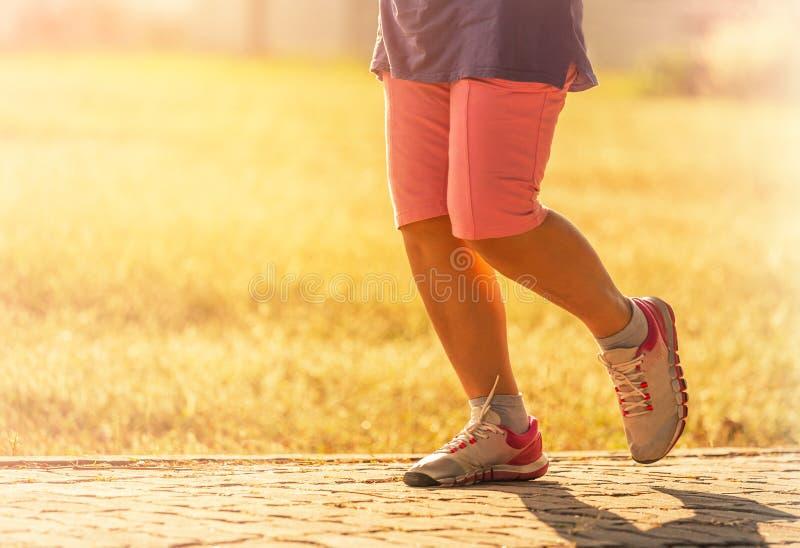 Πόδια γυναικών που στο δρόμο στο ηλιοβασίλεμα στοκ εικόνα