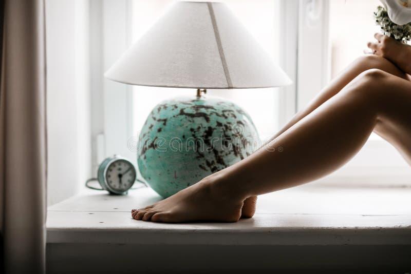 Πόδια της νέας γυναίκας στο windowsill στοκ εικόνες