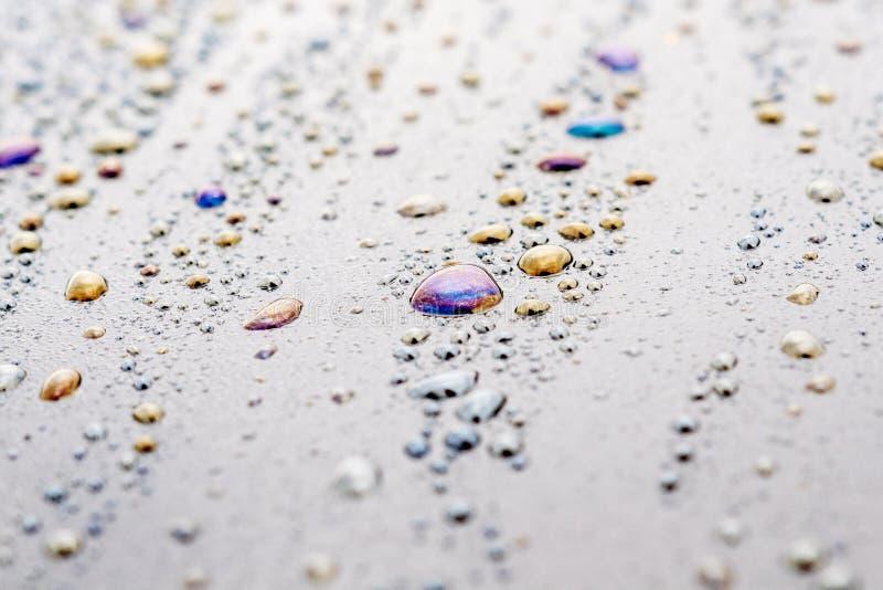 Πτώσεις με τους λεκέδες των διαφορετικών χρωμάτων, νερό με τα προϊόντα πετρελαίου σε μια σκοτεινή επιφάνεια, διάφορες πτώσεις στοκ εικόνα