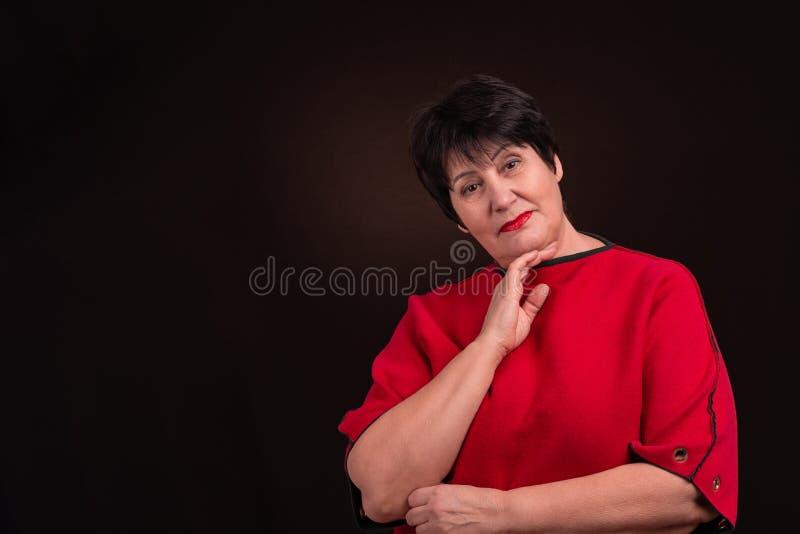 Πυροβολισμός στούντιο μιας ανώτερης ενήλικης σοβαρής γυναίκας που φορά ένα κόκκινο φόρεμα σε ένα σκοτεινό υπόβαθρο Εξετάζει ήρεμα στοκ εικόνες