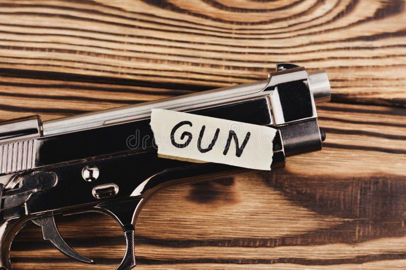 ΠΥΡΟΒΟΛΟ ΌΠΛΟ επιγραφής σε σχισμένο χαρτί και το στιλπνό πιστόλι στοκ εικόνα